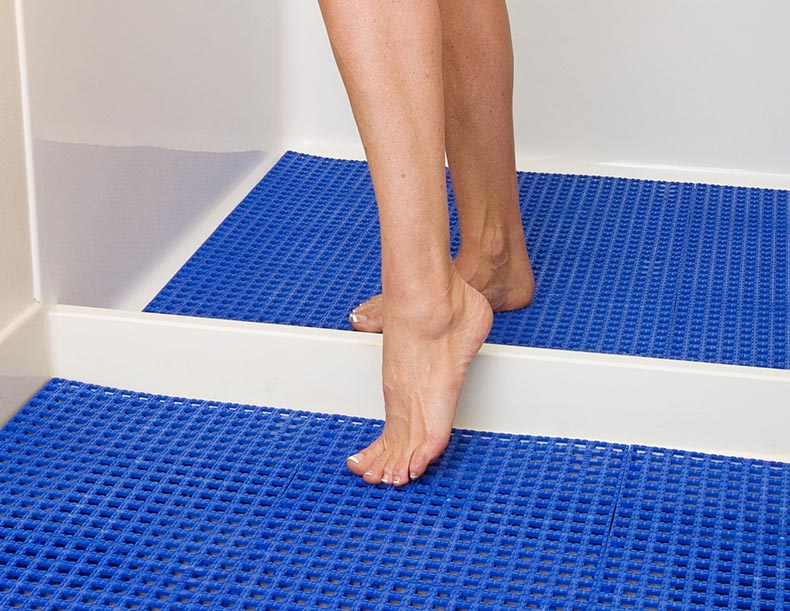 Shower mats used by woman getting out of the shower, indoor flooring